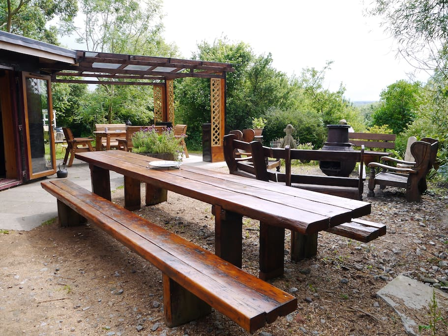 Outdoor banqueting table and seating around pot bellied stove.