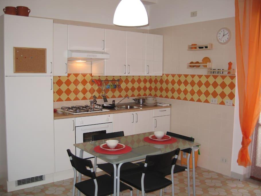 Cucina 3 mt. tavolo, 4 sedie, forno, microonde, frigorifero nell'ambiente soggiorno