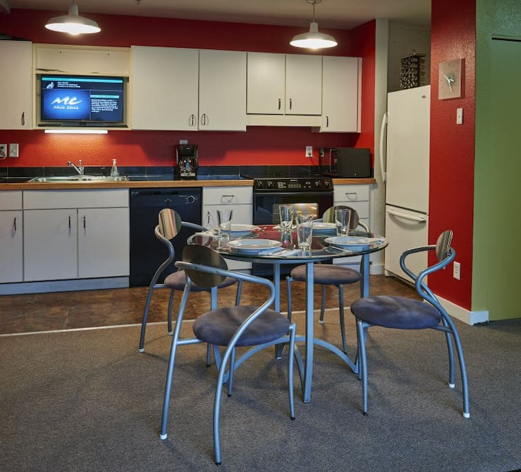 Full kitchen and dining area has flat screen TV.