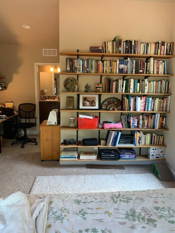 When we don't have guests, this is the library. Feel free to browse the shelves. On the left is a large desk alcove with drawers, shelves, and comfortable office chair.