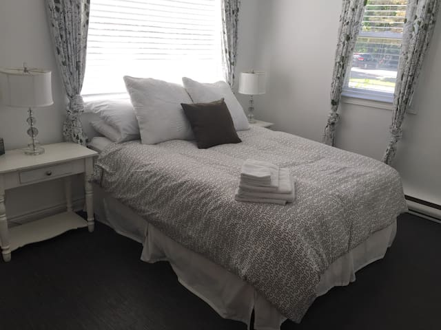 Main level bedroom with queen bed and direct access to bathroom.