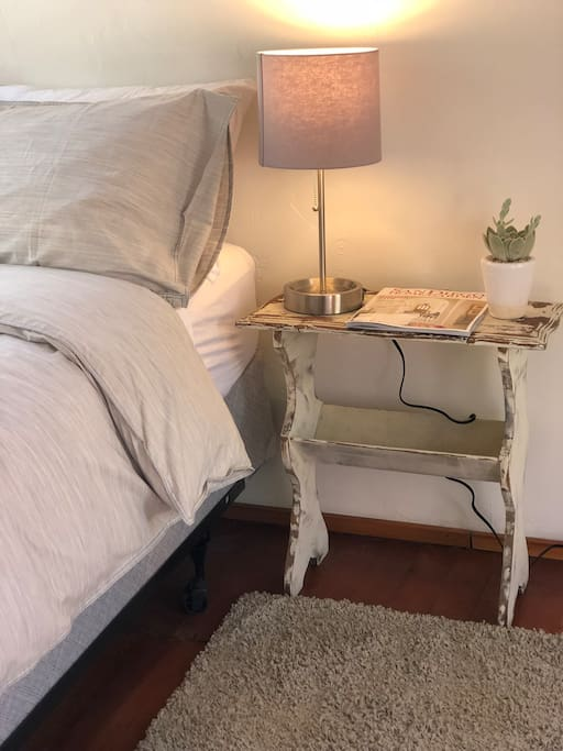 Bed, nightstand and lamp with outlet for charging phone
