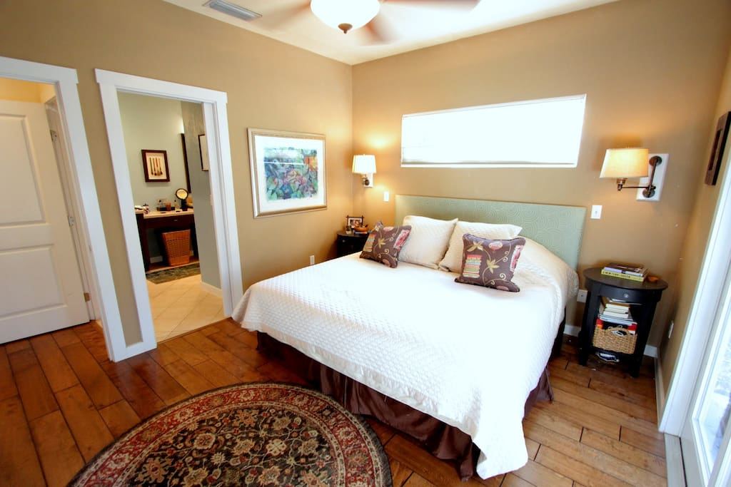 The master bedroom has a queen-sized bed, a walk-in closet, French doors that open to the backyard and has an attached bathroom.