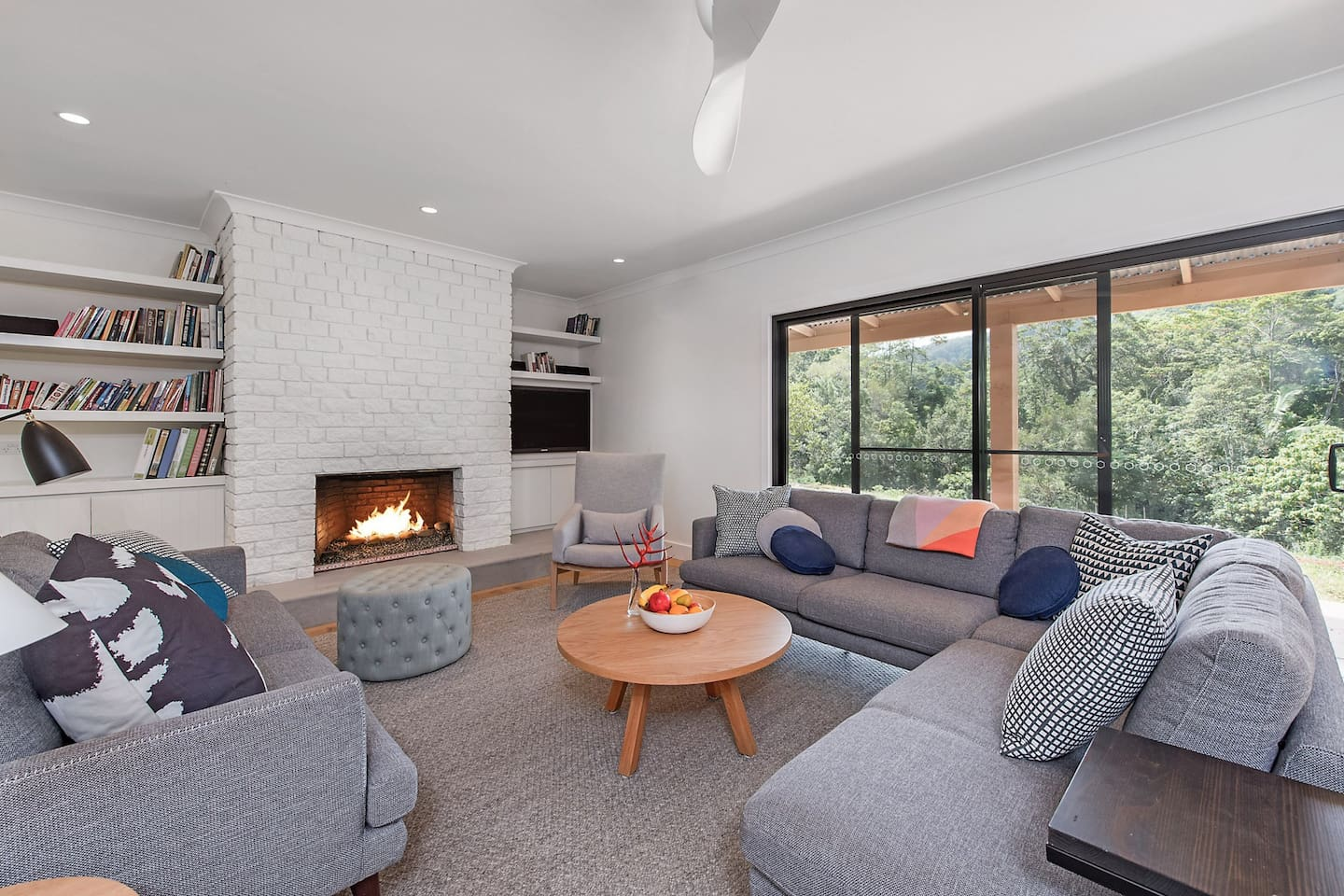 Lounge room with open fireplace and garden view