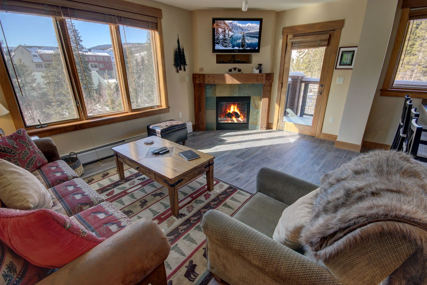 A big living room with TV and fireplace with a great view of the mountains