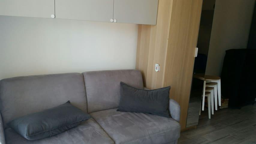 canapé lit avec penderie sur le coté et placard de rangement au dessus