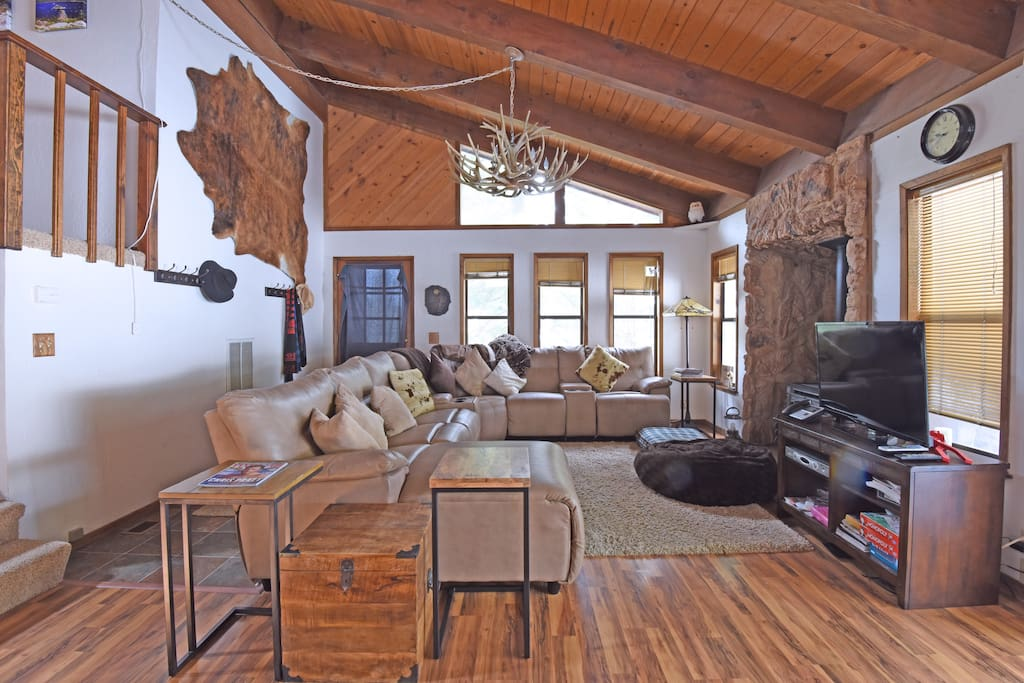 Living room with spacious couch, flat screen TV, and gas fireplace