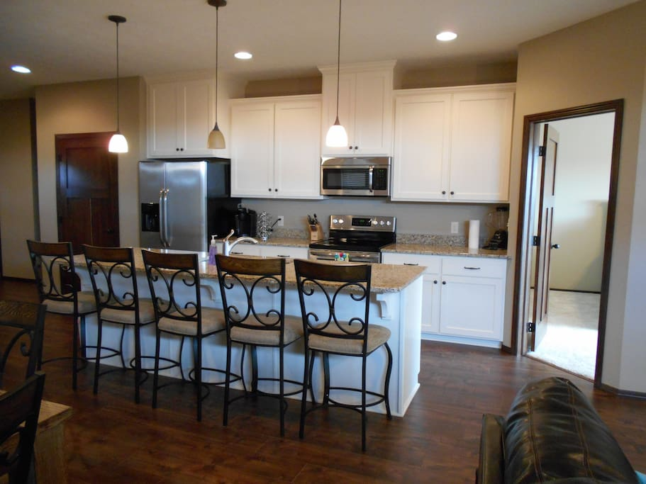 Bright airy kitchen with large island, granite countertops, and stainless steel appliances.