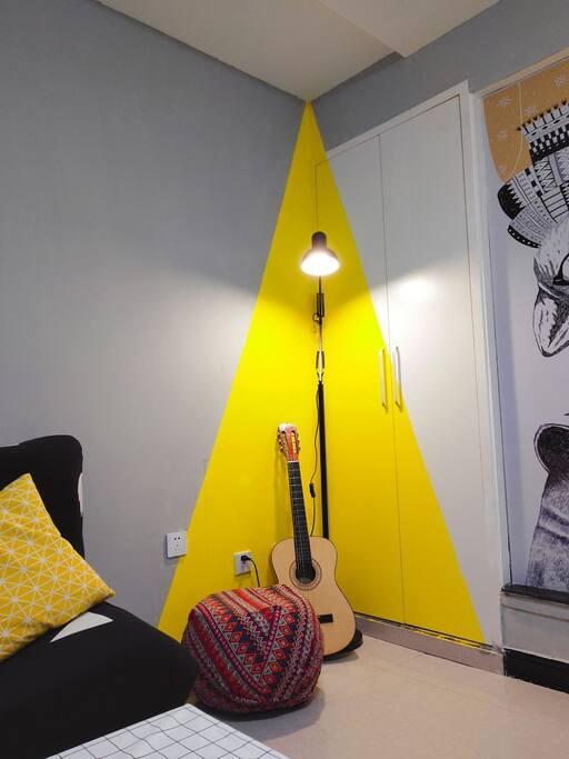 客厅的另一角,落地灯配着明亮的黄色,可以坐在小矮凳上看书,阳光角还有一把爸爸辈的老吉他。