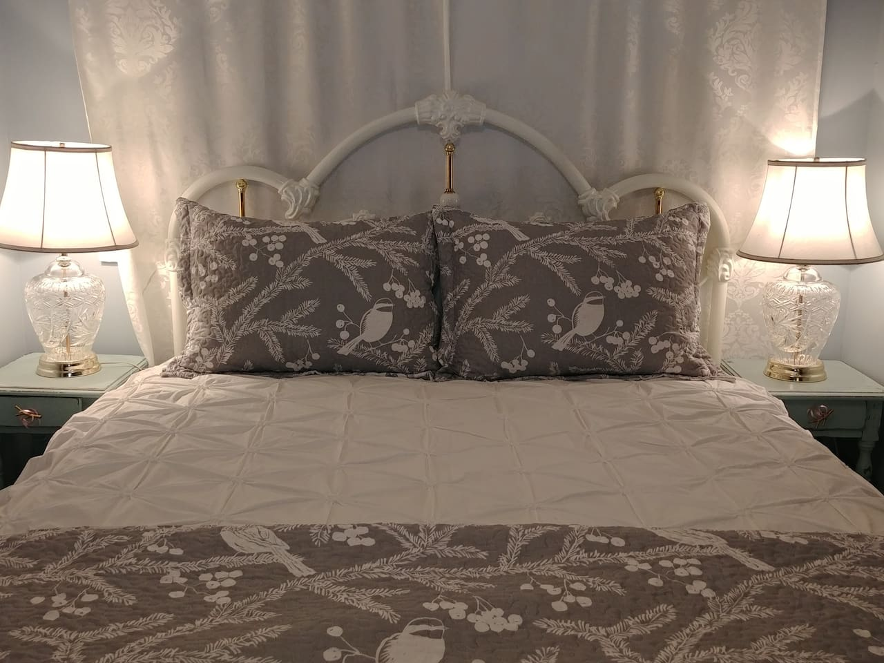 Bedspread theme: Birds on Snowy Branches. This bed is in the cozy bedroom with an antique wardrobe