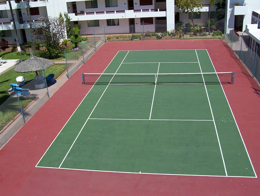 The tennis court next to the pool.