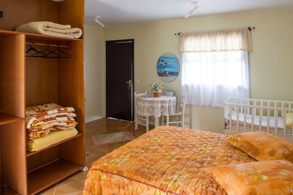Quarto com cama de casal, gurda roupa, Mesa para trabalho, televisão, frigobar.