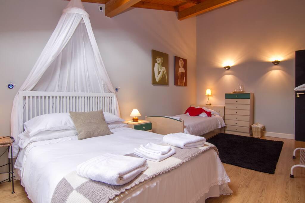 Una habitación abuhardillada, con altos techos de madera,  una ventana y una claraboya