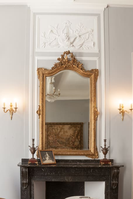 Marble fireplace and lovely ornate mirror above in a French apartment in the South of France with light grey walls and beautiful moldings. #fireplace #luxurious #French #apartment