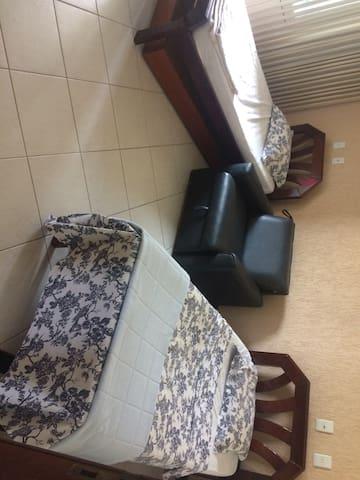 Quarto com duas camas de solteiro e banheiro