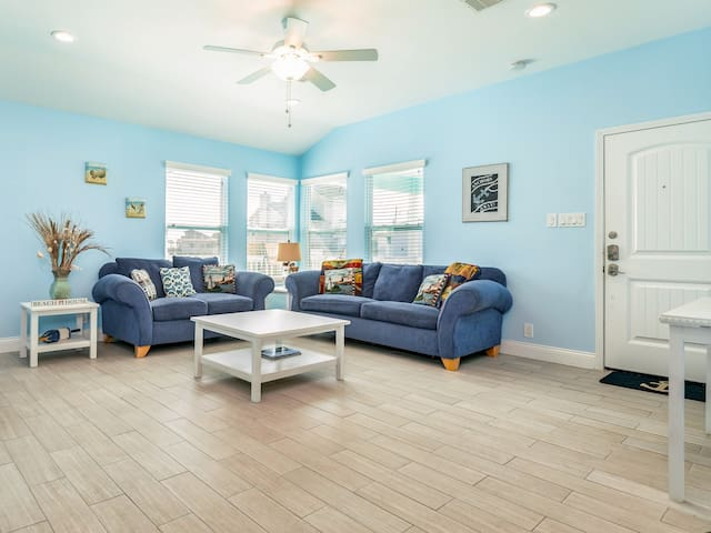 Open-plan living area with comfortable seating for six. Professional housekeeping services provided by TurnKey.
