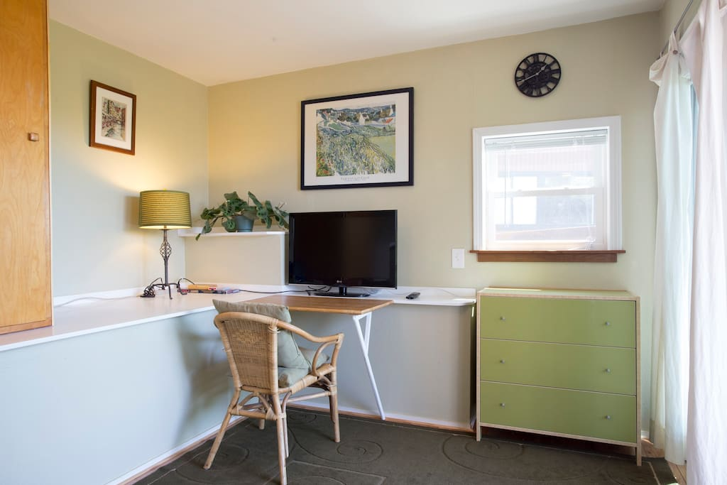 Room features a fold-up desk, TV, dresser and armoire with hangers