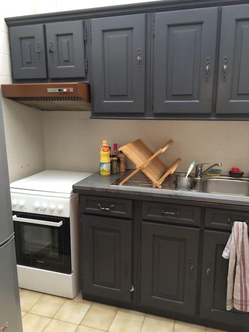 Cuisine équipée d'un four et cuisinière au gaz, machine à laver, cafetière et grille pain.