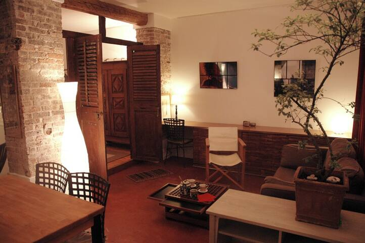 Warm living room with terracota tiles, bricks and beams.