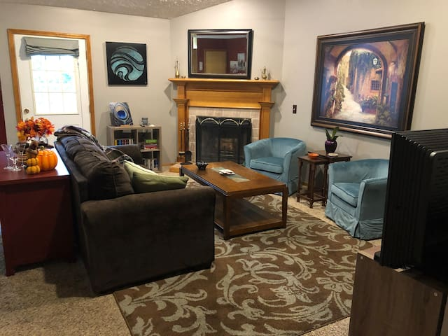 Spacious living room with comfortable seating for 5 that opens to the dining area and back yard. Cathedral ceiling, wood-burning fireplace, and TV will give you a great place to kick back and relax during your stay.