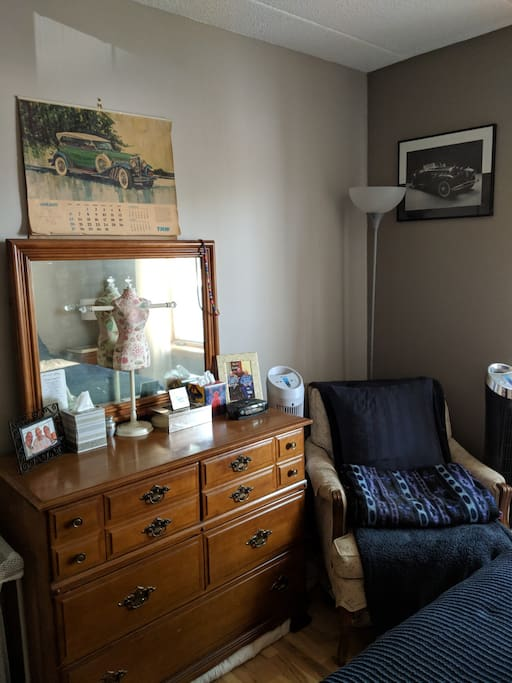 Dresser (top half empty) and reading chair.