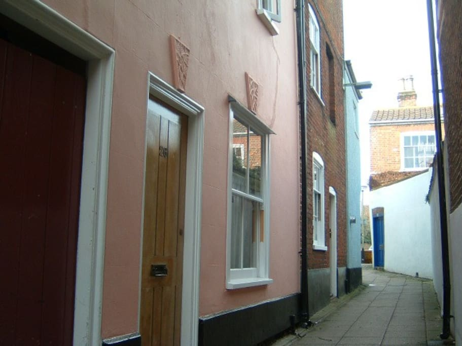 You're actually coming to two seventeenth-century terraced houses: the pink # 26 and the brick # 24. Vehicle access is just round the corner.