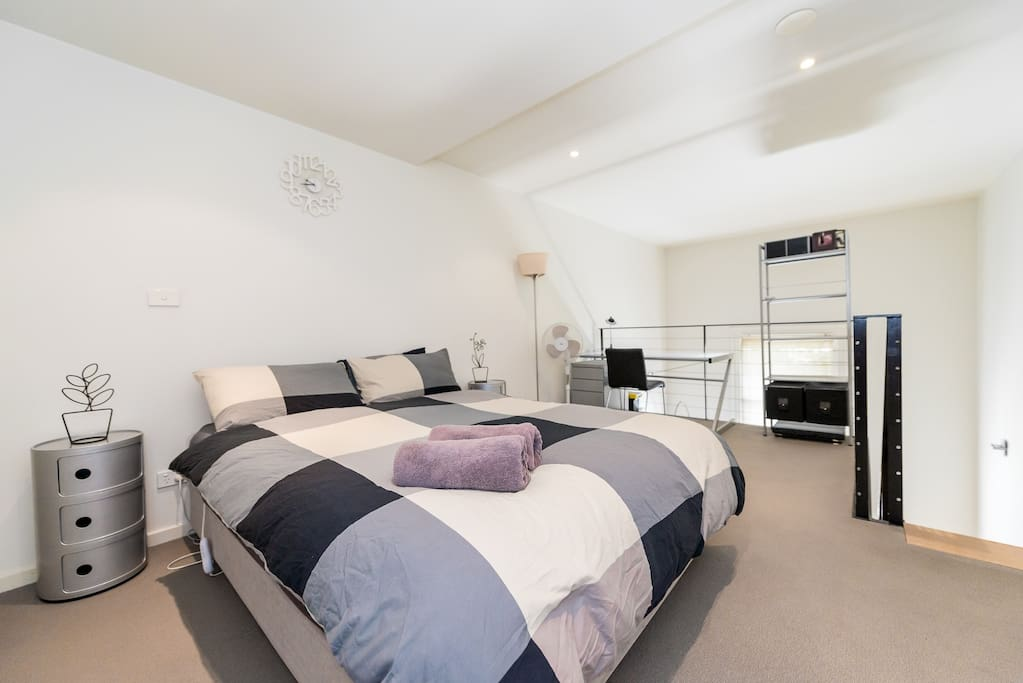 An open plan bedroom with a queen sized bed, study & en-suite.