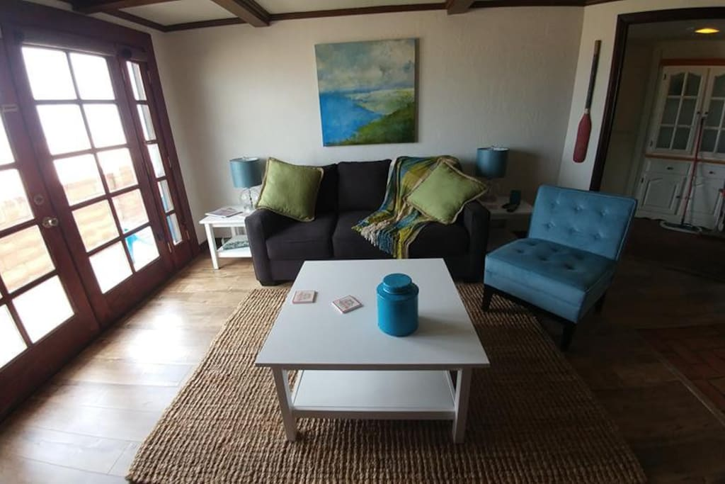 Living Room with beach and ocean views and sofa sleeper, HD flat screen TV, and open, full kitchen to right