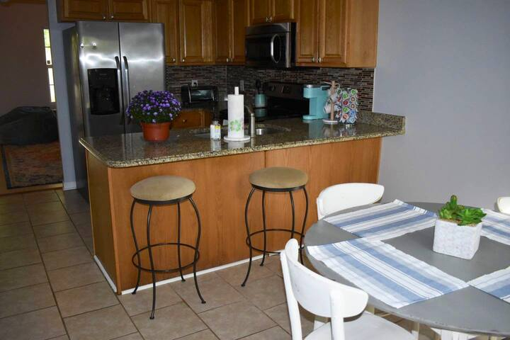 Fully stocked kitchen with breakfast table, barstools, and coffee station