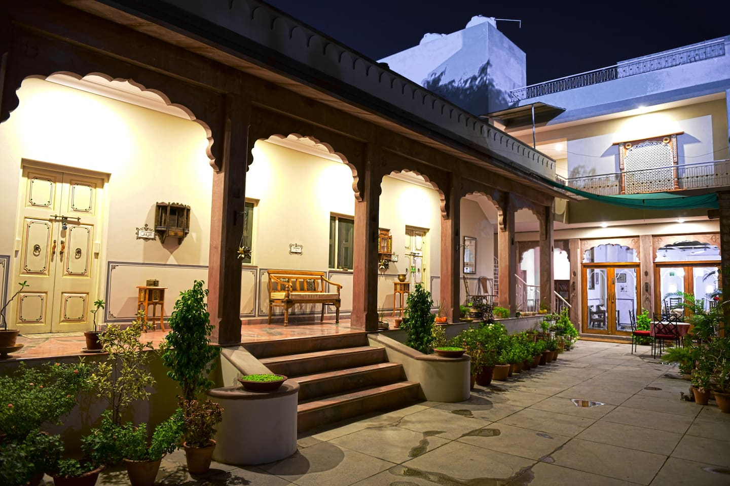 A private, cozy hideout, having 3 ground floor rooms and 2 rooms on the 1st floor. The dining room is located on the ground  floor. These rooms have a spacious courtyard to unwind, with lots of potted plants. This is a night view of the front facade.