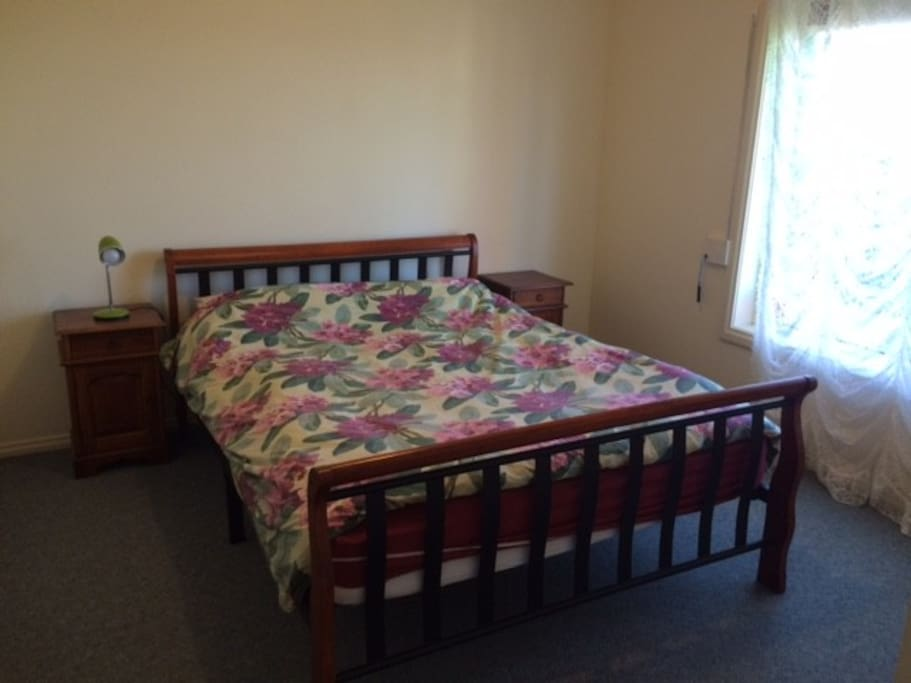 The large main bedroom with queen bed, built ins, ensuite and garden view.