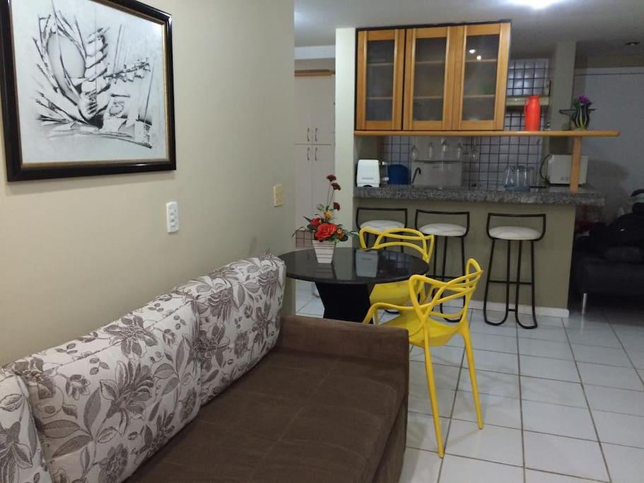 Apartamento com cozinha do tipo americana toda equipada com geladeira, forno microondas, forno elétrico, fogão, vasilhas, talheres, pratos... cozinha completa