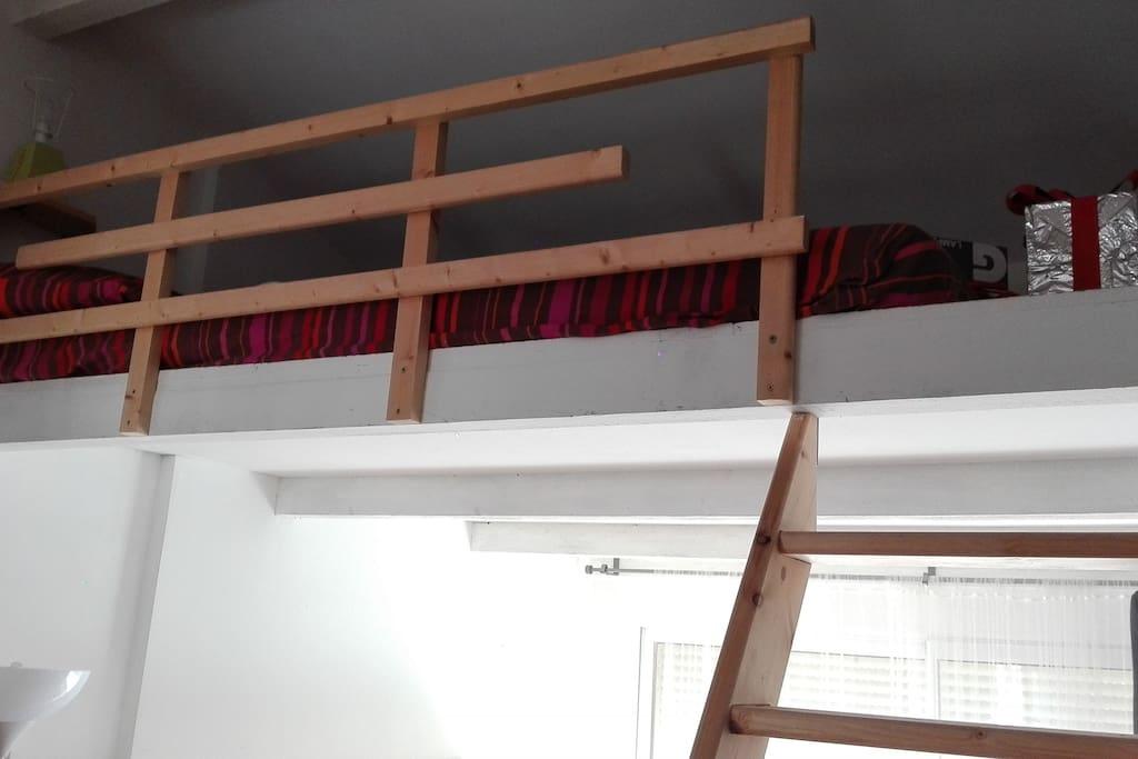 Matelas double à l'étage. Mezzanine équipée d'une lampe de chevet, et de prises pour charger téléphones et tablettes