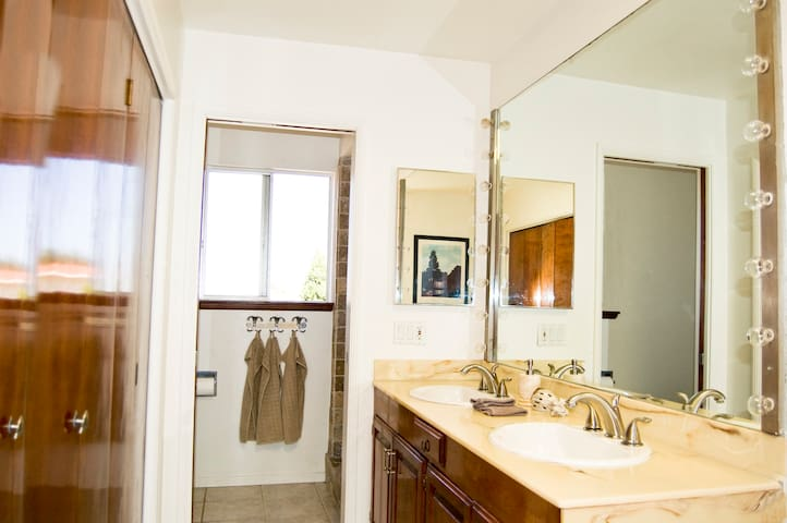 Upstairs bathroom with double sinks, and private toilet & shower area