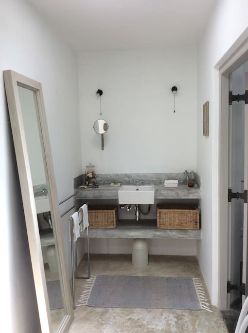 Spacious airy bathroom with semi outdoor shower.