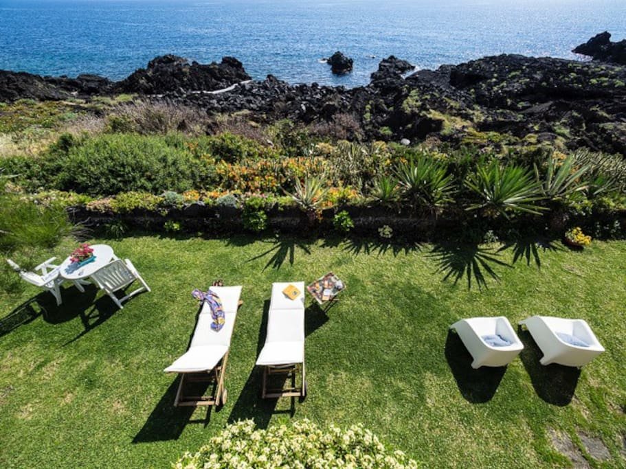 The garden borders on the lava rocks by the sea