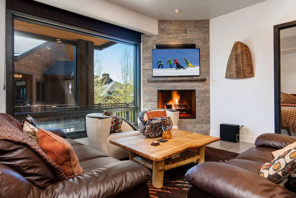 In the living room, handsome loveseats and a set of streamlined sitting chairs invite movie nights, board game sessions, and afternoon naps by the gas fireplace.