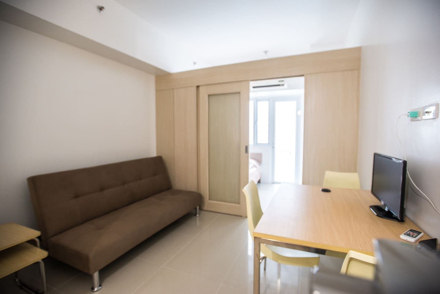 The living space has a sofa bed (which goes flat), a dining table and small TV. The double bed is behind the partition and faces the communal pool area outside.