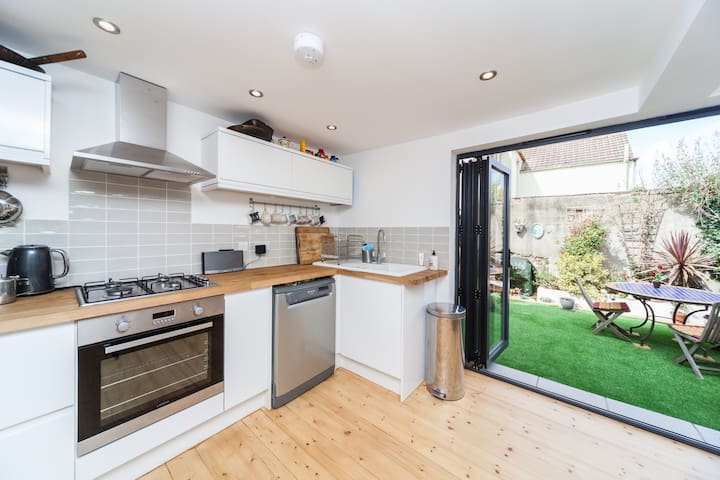 Well equipped modern kitchen with bifold doors opening onto garden