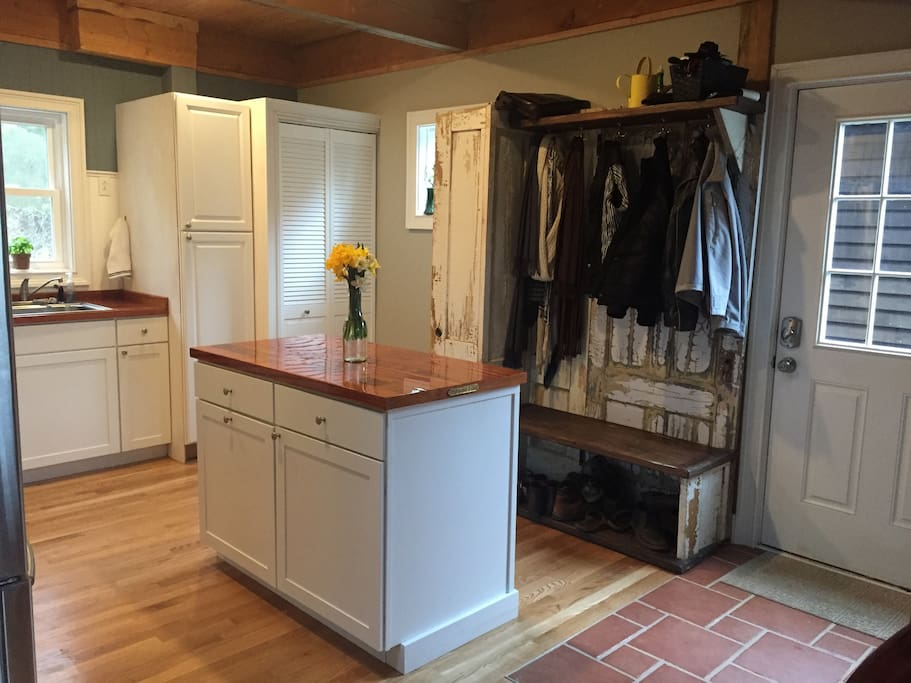 Stacked washer and dryer behind the bifold doors. NOTE: the bench was made from antique doors, unknown if they contain lead paint or not.