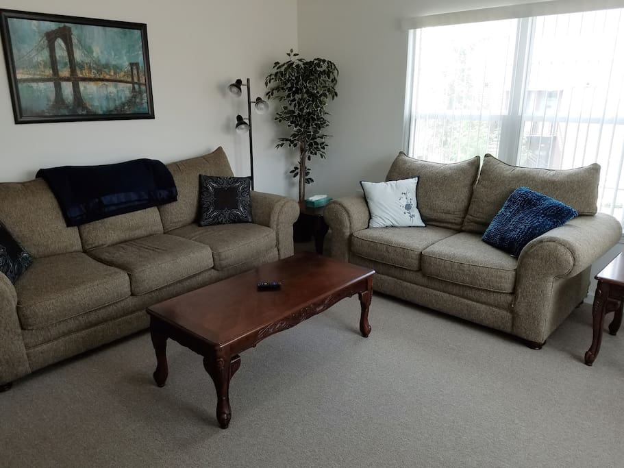 A comfortable living room  with plenty of seating and smart TV.