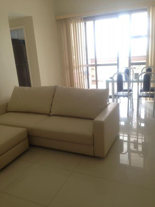 Sala ampla e arejada com sofá, puff, tv e mesa de jantar + varanda com mesa redonda com 4 cadeiras.