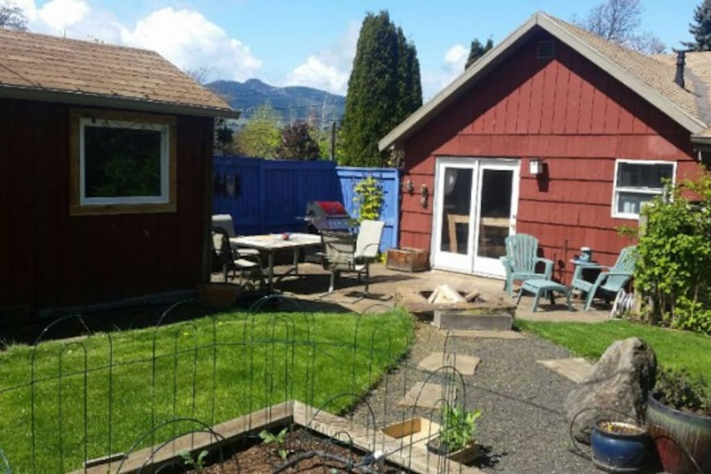 Private backyard includes BBQ, table, fire pit, raised garden beds and green house.