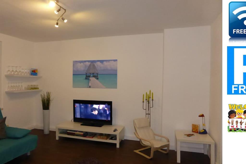 Wohnzimmer mit Fernseher und Kinderecke.