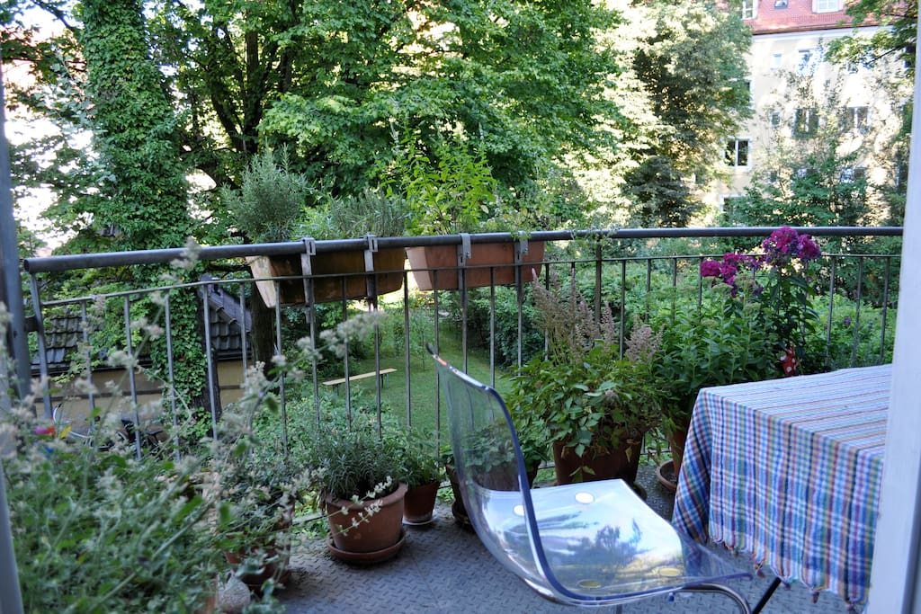 Rear balcony overlooking a lush, green garden.