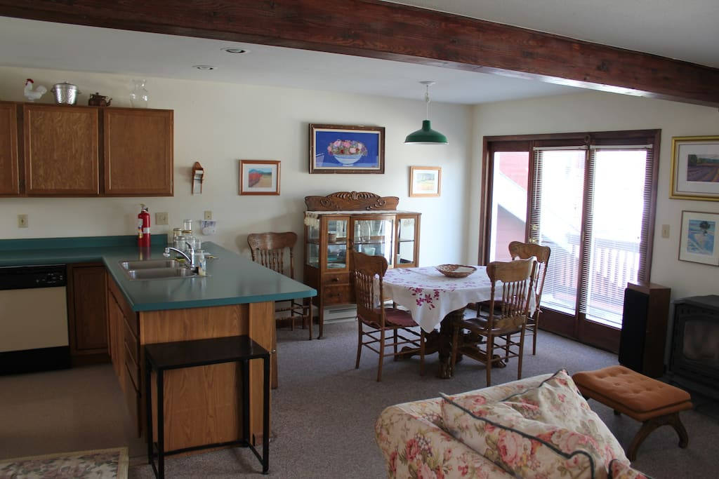 Open floor plan with fully equipped kitchen, gas cast iron stove in the living area and gas grill on the balcony.
