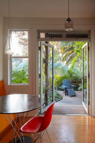 Kitchen with eating nook opens to private palm garden in back, with deck and heated sofa.