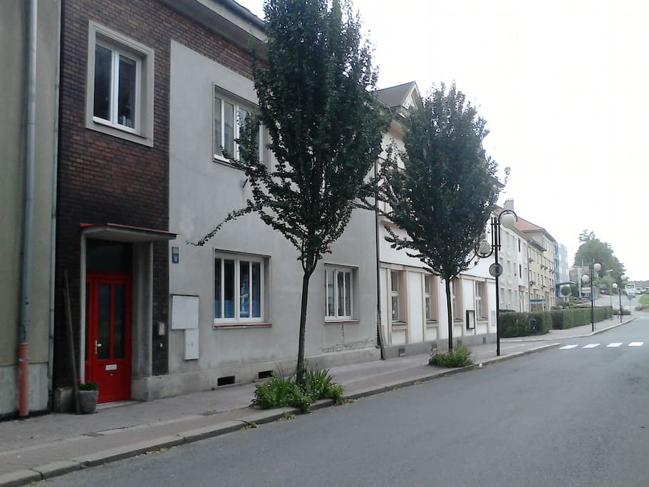 The house has red door and is placed on a quiet street in the center of the town