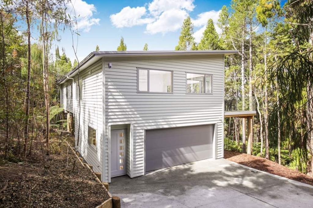 At the top of a ridge, at the end of a long driveway. A perfect retreat. Our home in the native bush. Completed in Sept 2015 it is one of three properties on a protected natural ridge at the edge of the Waitakere Ranges Regional Park.