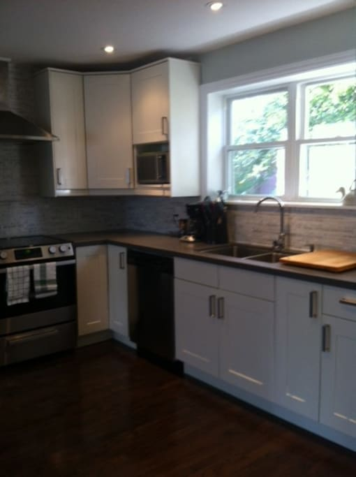 Kitchen has solid quartz countertops, stainless appliances and stocked with condiments & spices!